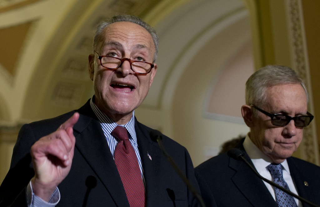 Sen. Charles Schumer, D-NY, left, is joined by Senate Minority Leader Harry Reid, D-NV, as Schumer speaks to the media after a policy luncheon on Capitol Hill on Wednesday, July 8. Senators unveiled a bipartisan framework aimed at making business taxes more competitive while generating funding to repair the nation's roads and bridges. (AP Photo/Carolyn Kaster)