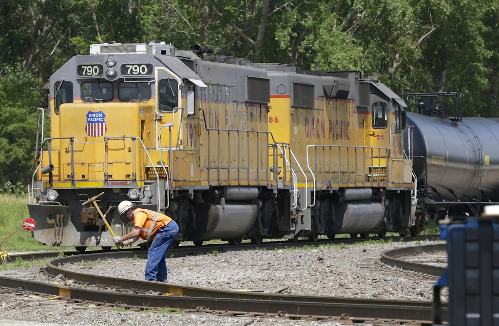 An employee performing maintenance on the tracks in front of a Union Pacific train in Council Bluffs, Iowa. (AP Photo/Nati Harnik)
