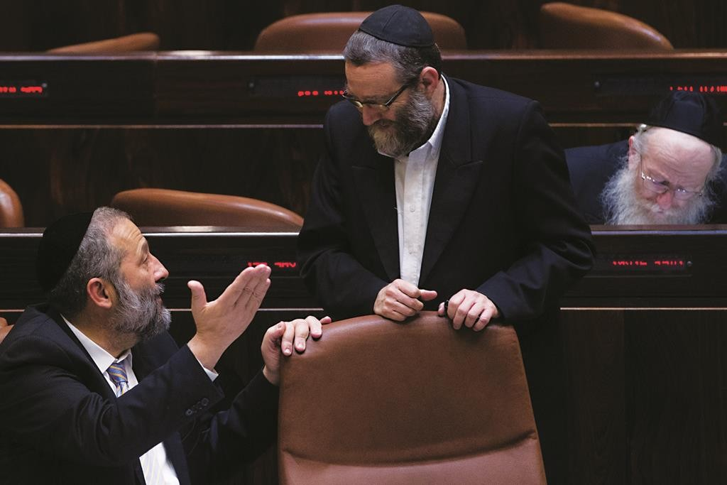 Shas leader Aryeh Deri (seated) speaking with Rabbi Moshe Gafni of the United Torah Judaism party during a recent plenum session in the Knesset. (Miriam Alster/FLASH90)