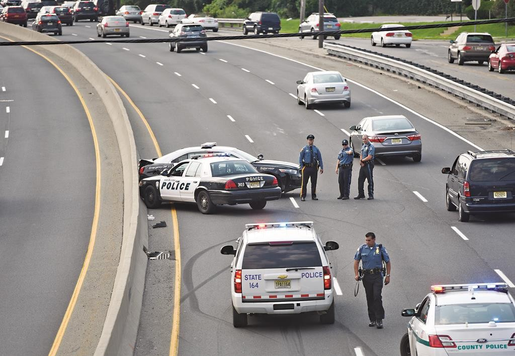 Police on Sunday stand near two police cars that were involved in an accident during a police chase of Sereymanta Kong in Paramus, N.J. (Tyson Trish/The Record via AP)