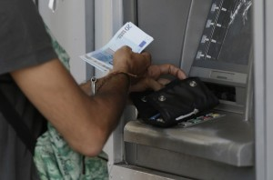 A man uses an ATM of a bank after the government's decision last week to limit daily cash withdrawals to 60 euro ($66) in Athens, Tuesday.  (AP Photo/Petr David Josek)