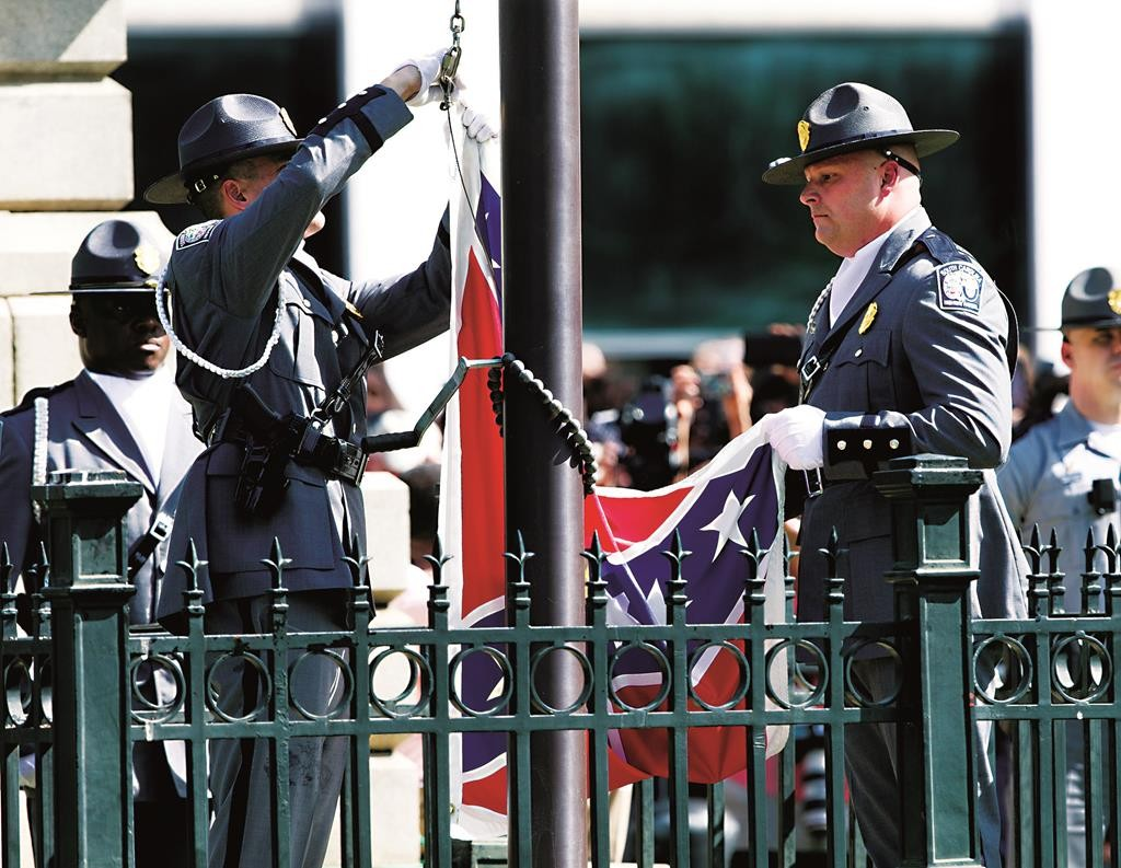 An honor guard from the South Carolina Highway patrol lowers the Confederate battle flag as it is removed from the Capitol grounds in Columbia, S.C.  (AP Photo/John Bazemore)