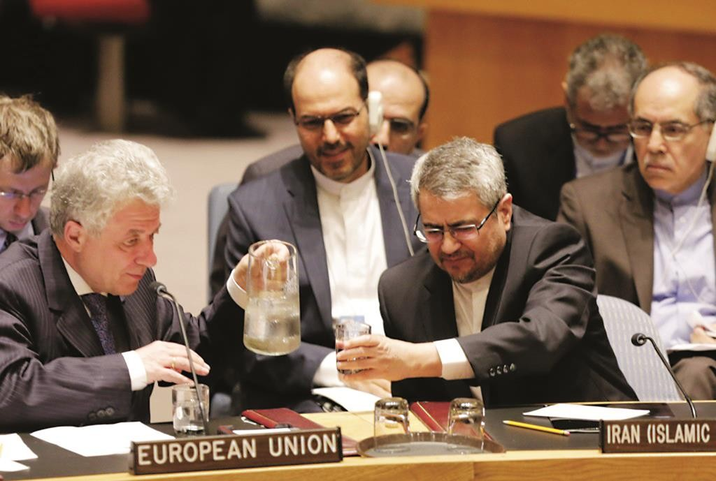 Thomas Mayr-Harting (L), head of the delegation of the EU to the United Nations, pours a glass of water for Iran's U.N. Ambassador, Gholamali Khoshroo, at United Nations headquarters on Monday. (AP Photo/Mark Lennihan)