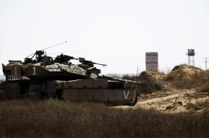 An Israeli army tank takes position along Israel's border with Egypt's North Sinai (seen in background) Wednesday.  (REUTERS/Amir Cohen)
