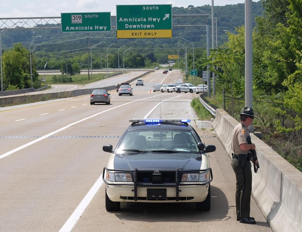A highway patrolman stands guard atop the C.B. Robinson Bridge. Police and emergency vehicles fill Amnicola Highway after two attacks Thursday morning, one at a recruiting center and another that killed four Marines at a military site a few miles away, in Chattanooga, Tenn. (Tim Barber/Chattanooga Times Free Press via AP)