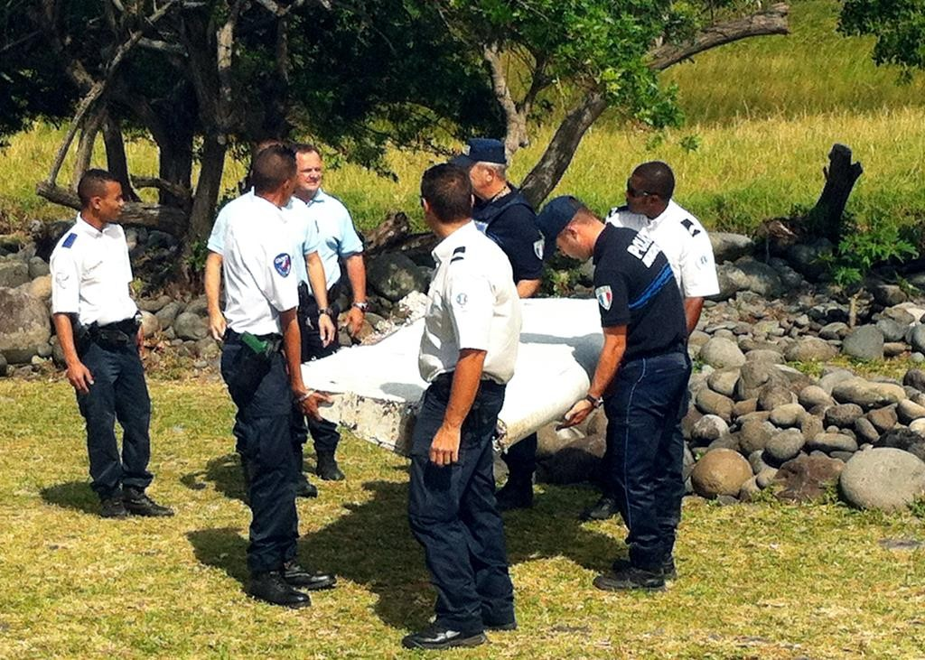 "Police carry a piece of aircraft debris found in the eastern coastal area of the French Indian Ocean island of La Reunion, on Wednesday. Air safety investigators have a ""high degree of confidence"" that the debris is of a wing component unique to the Boeing 777, the same model as the Malaysia Airlines plane carrying 239 passengers and crew that disappeared without a trace last year.  (Yannick Pitou/AFP/Getty Images)"