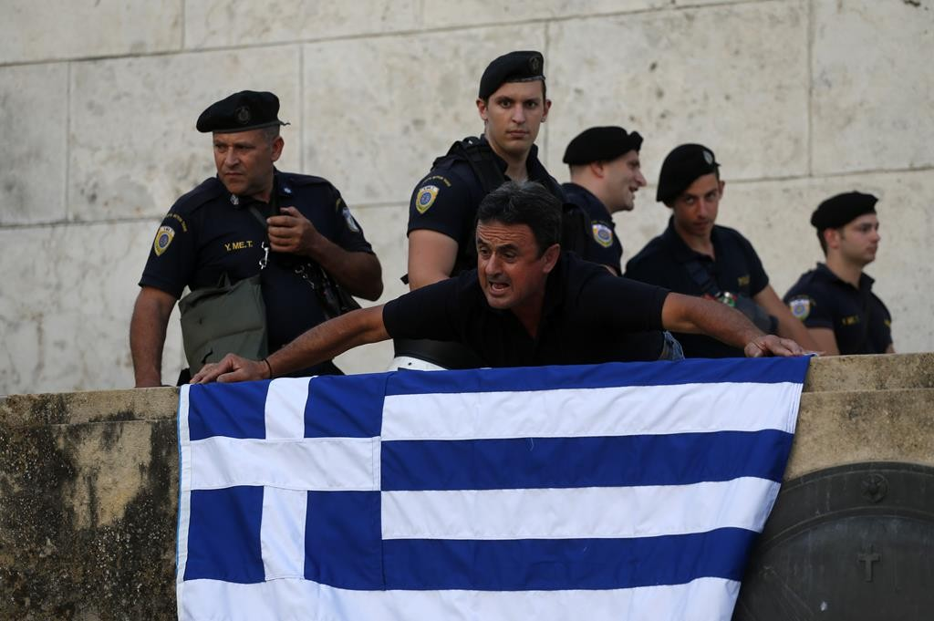 An anti-austerity protester in Athens positions a Greek flag during a rally against the government's agreement with its creditors, as riot police guard one of the entrances of the Greek Parliament, Monday. (AP Photo/Emilio Morenatti)