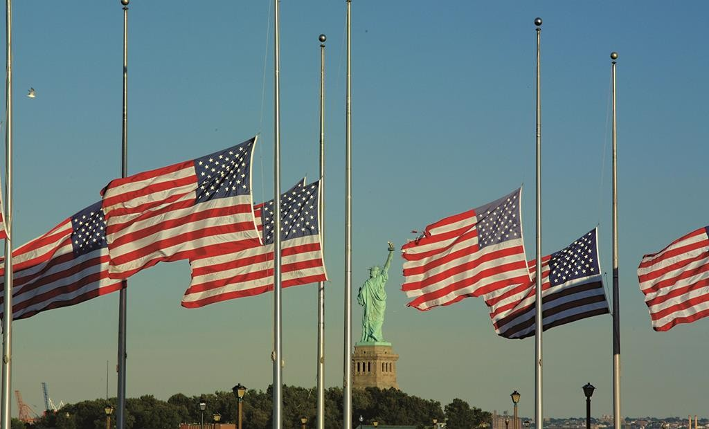 American flags overlooking the Statue of Liberty fly at half staff. (Flickr)