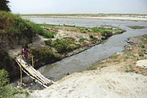 An man crosses a bamboo bridge over a polluted tributary that runs into the river Ganges in Kanpur. (Sanjay Kanojia/AFP/Getty Images)