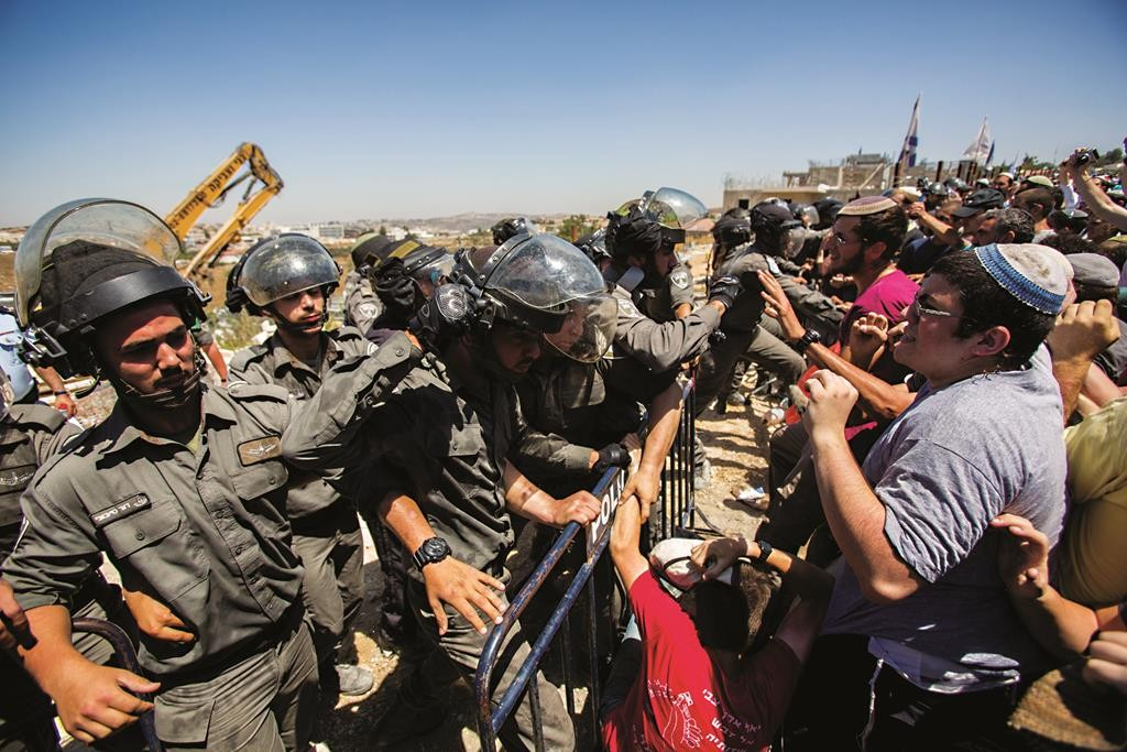 Israeli security forces scuffle with Jewish protesters in Beit El as illegal structures were demolished. Heavy equipment can be seen in background. (Yonatan Sindel/Flash90)