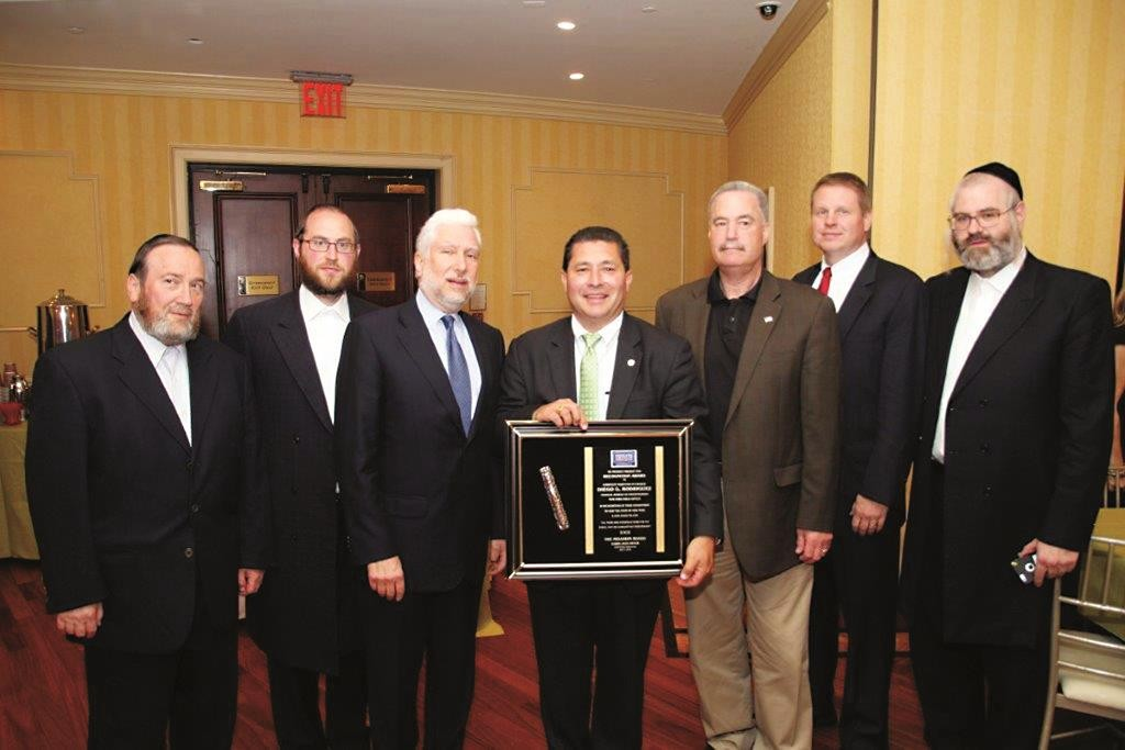 Assistant director in charge of FBI's New York field office Diego Rodriguez (C), together with other participants at a recent meeting, displays his award,.