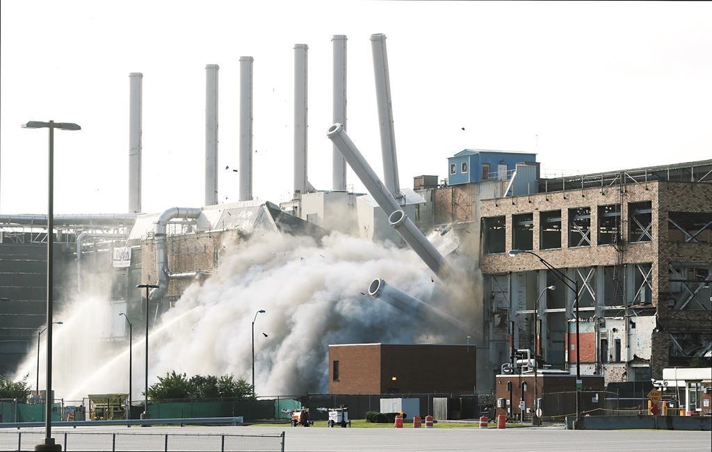 Smokestacks fall Saturday during the implosion of Kodak Building 53 in Rochester.  (Carlos Ortiz/Democrat & Chronicle via AP)