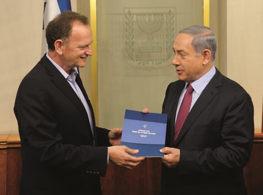 Maj. Gen. Yohanan Locker (Res.) submits the Locker committee report on the defense budget to Israeli Prime Minister Binyamin Netanyahu. (Amos Ben Gershom/GPO)