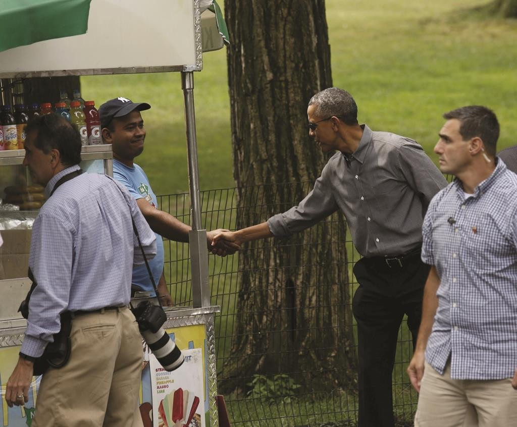 President Barack Obama on Saturday shakes hands with a vendor while walking in Central Park. (Reuters/Kevin Lamarque)