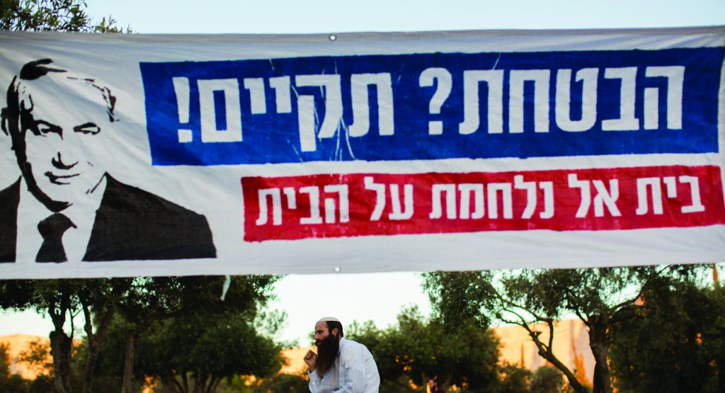 The sign calls on Prime Minister Binyamin Netanyahu to keep his campaign promise to strengthen the Jewish presence in Yehudah and Shomron, at a demonstration urging cancellation of the plan to evacuate a neighborhood in Beit El.  (Yonatan Sindel/FLASH90)
