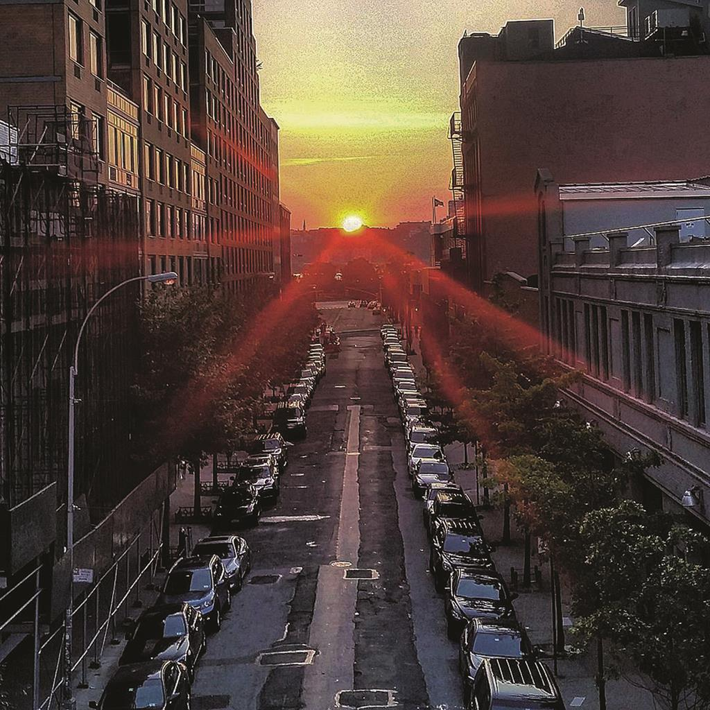 "The sun lines up Sunday evening with Manhattan's cross streets before setting, for ""Manhattanhenge."" (Flickr/Thomas V)"