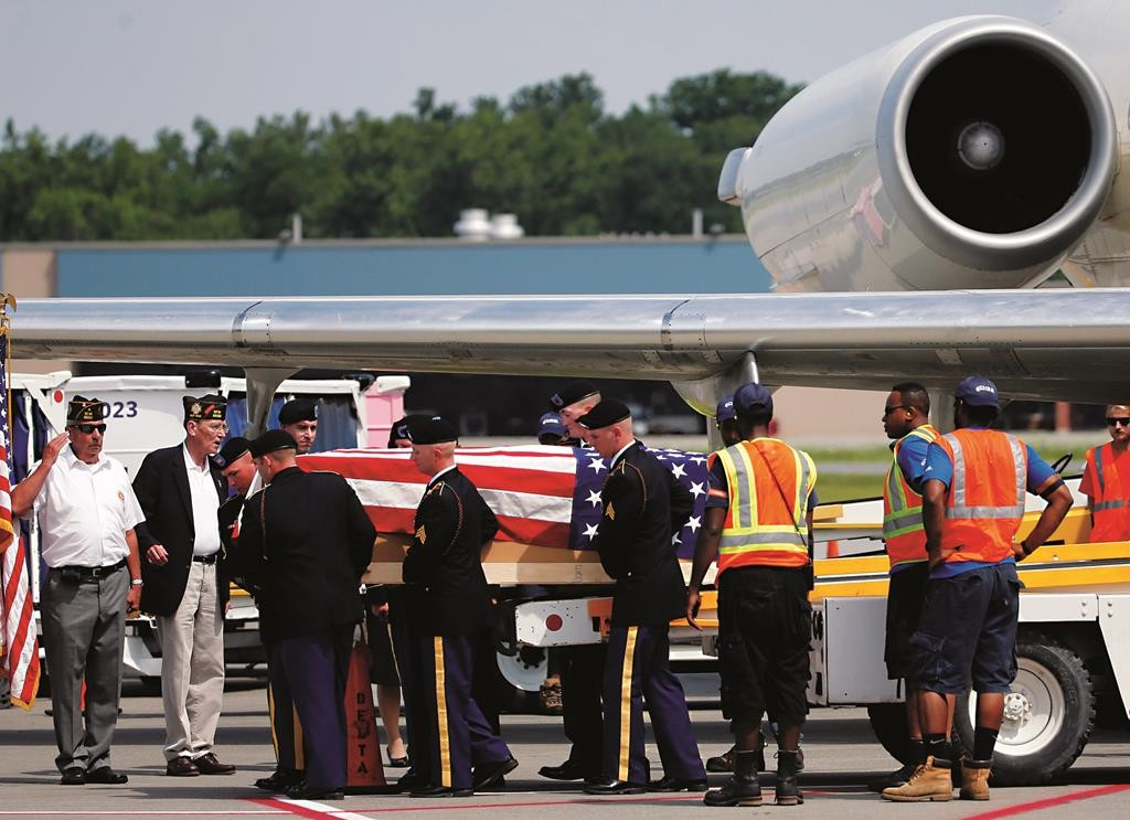 The remains of World War II fighter pilot Lt. Edward F. Barker are transferred on Wednesday from a commercial airplane to a waiting hearse at Albany Airport. (AP Photo/Mike Groll)