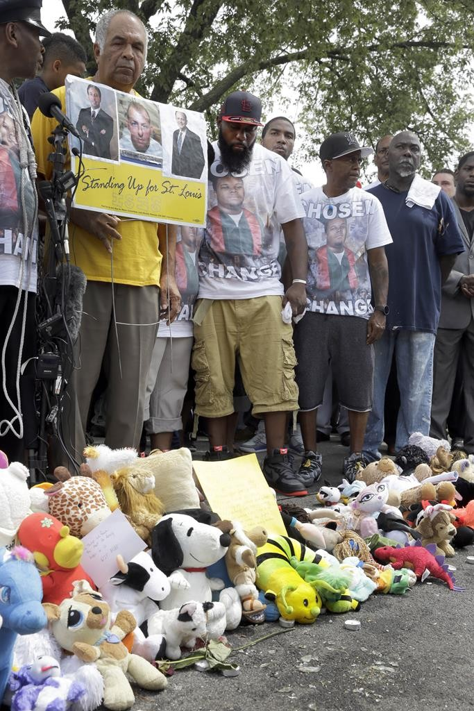Michael Brown Sr., (C), surrounded by family, friends and supporters pauses for a moment of silence at a memorial to his son Michael Brown, Sunday, in Ferguson, Mo. (AP Photo/Jeff Roberson)