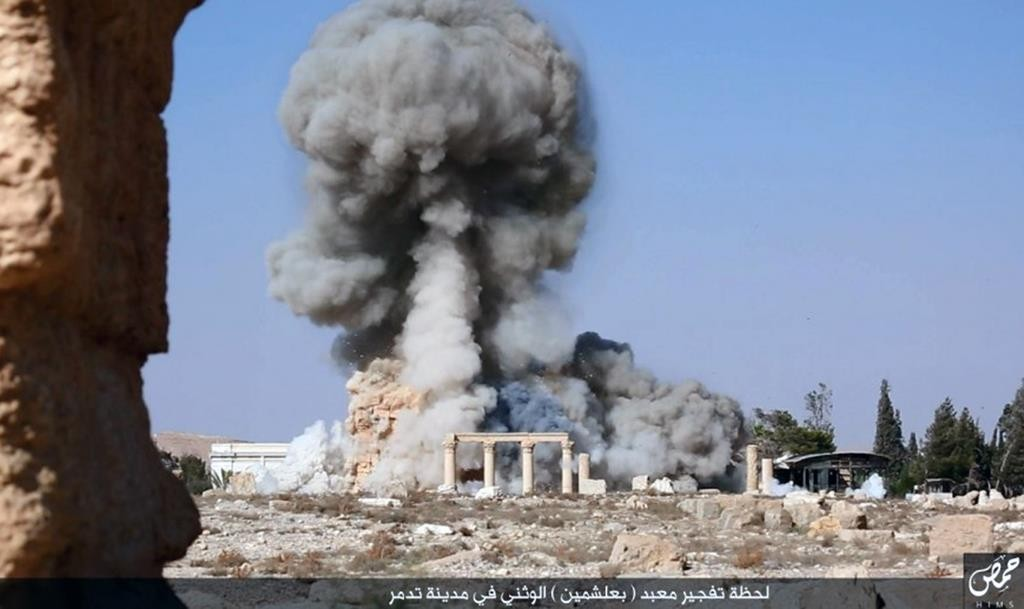 This undated file photo released Tuesday, on a social media site used by Islamic State terrorists, which has been verified and is consistent with other AP reporting, shows smoke from the detonation of the 2,000-year-old temple of Baalshamin in Syria's ancient caravan city of Palmyra. (Islamic State social media account via AP, File)