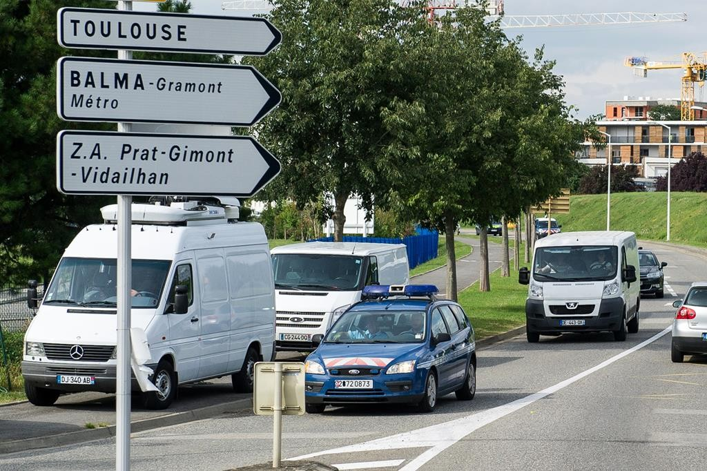 French police escort a white van (R) that transports debris found on a beach on Reunion island as it arrives at the military-run Direction generale de l'armement (DGA) offices laboratory that specializes in analyzing aviation wreckage in Balma, near Toulouse, France. (REUTERS/Stringer)