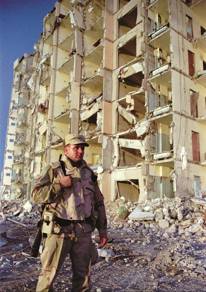 In this June 26, 1996 file photo, an unidentified U.S. soldier stands in front of the blast-shattered Khobar Towers housing complex, at a U.S. military base, that killed 19 Americans in Dhahran, Saudi Arabia.  (6AP Photo/Greg Marinovich, File)