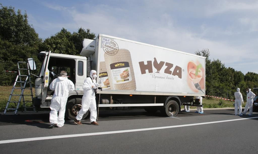 Forensic police officers inspect a parked truck in which up to 50 migrants were found dead, on a highway near Parndorf, Austria Thursday. (Reuters/Heinz-Peter Bader)