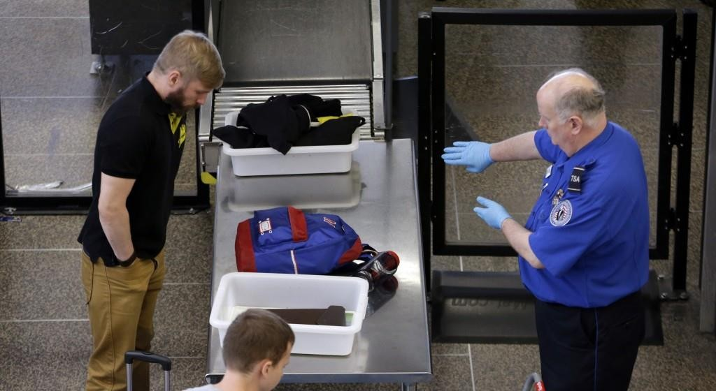 A TSA agent screening a passenger at Seattle-Tacoma International Airport.  (AP Photo/Elaine Thompson)