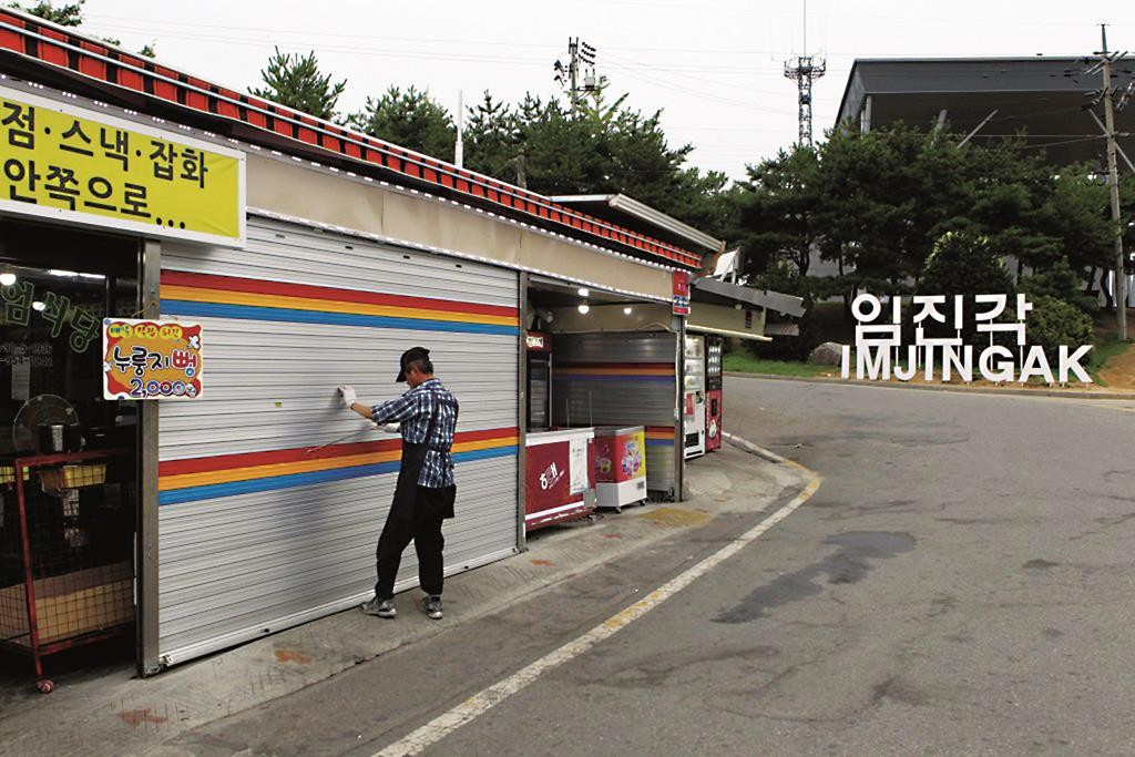 A man locks a shutter of his shop after an evacuation order is issued to the residents and visitors at the Imjingak Pavilion near the border village of Panmunjom, South Korea, on Thursday. (Kim Seung-doo/Yonhap via AP)