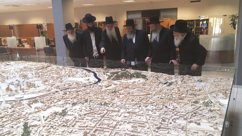 (R-L) Harav Schlesinger of Geneva, Harav Kotler, Rabbi Niederman, Harav Kalmanowitz, Rabbi Yecheskel Kalmanowitz and Dr. Schaps, viewing a miniature of the plan for the Sports Palace and the surrounding area in City Hall.