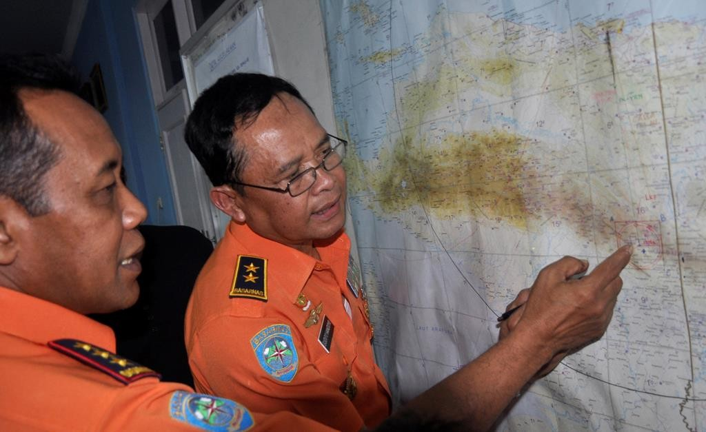 National Search and Rescue Agency (BASARNAS) chief F. Henry Bambang Soelistyo (L) looks at a map with Air Vice-Marshal Sudipo Handoyo during a search operation for the missing Trigana Air Service flight at Sentani airport in Jayapura, Papua province, Indonesia, Monday. (AP Photo/Alfian)