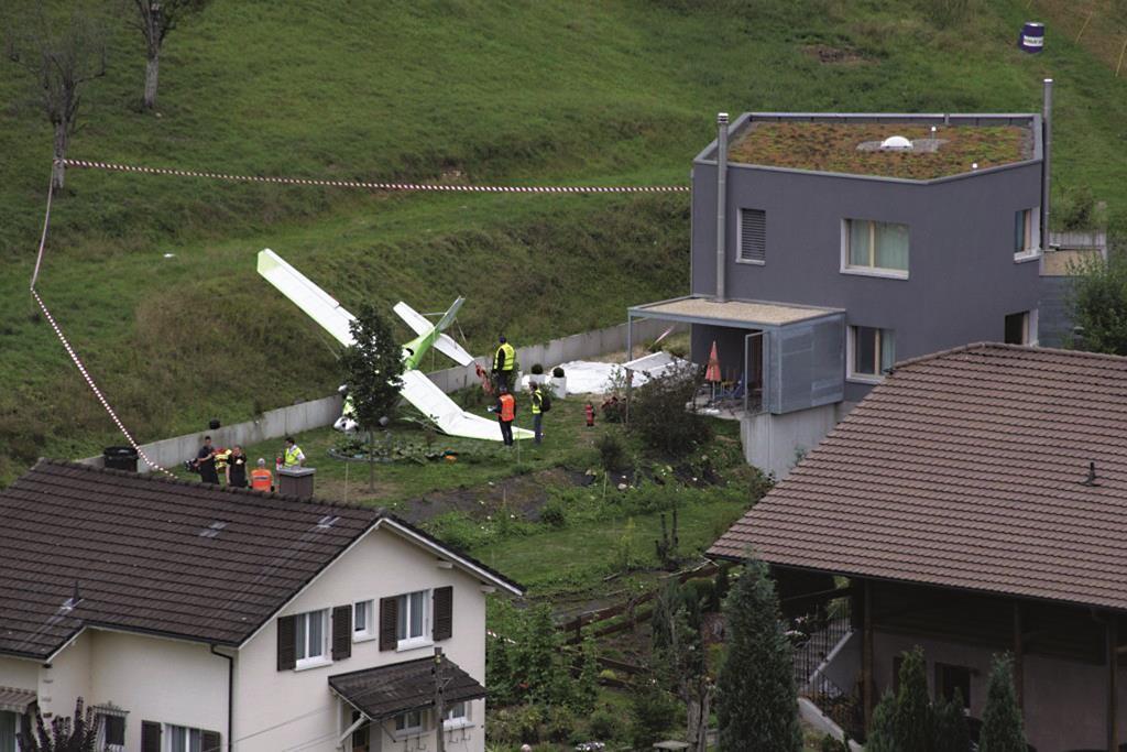 Firefighters stand beside a crashed plane, Sunday, in Dittingen, Switzerland.  (Georgios Kefalas/Keystone via AP)