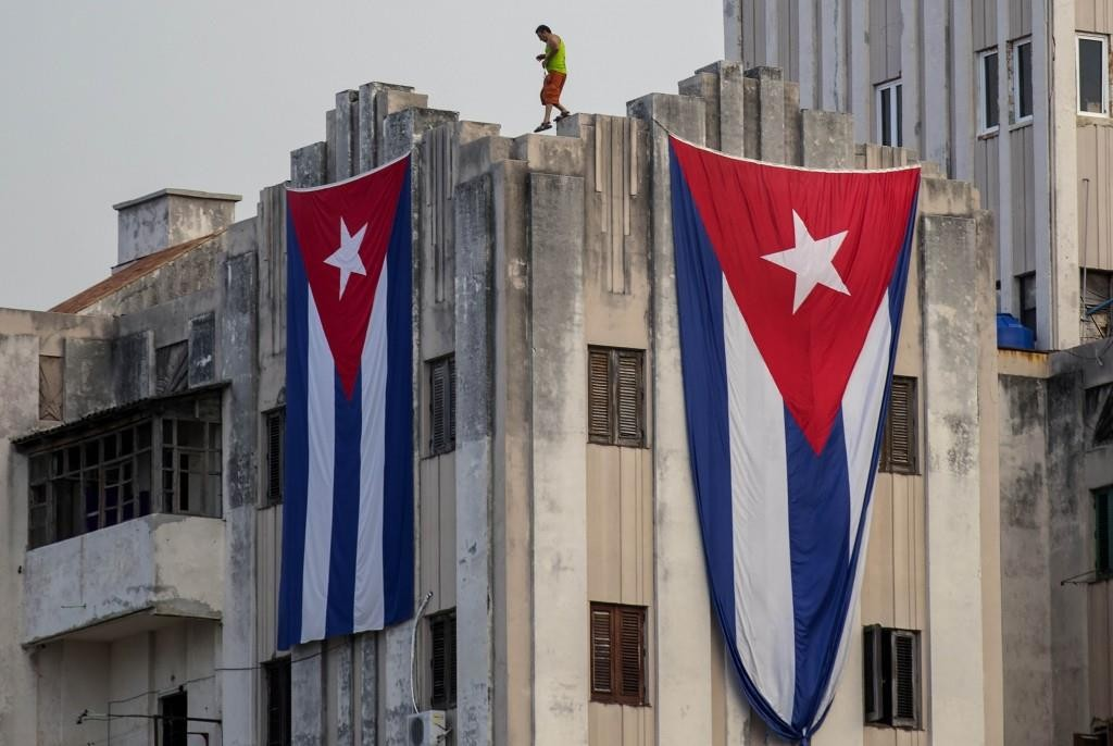 A man hangs Cuban flags at a building next to the U.S. embassy in Havana on Tuesday.  (AP Photo/Ramon Espinosa)