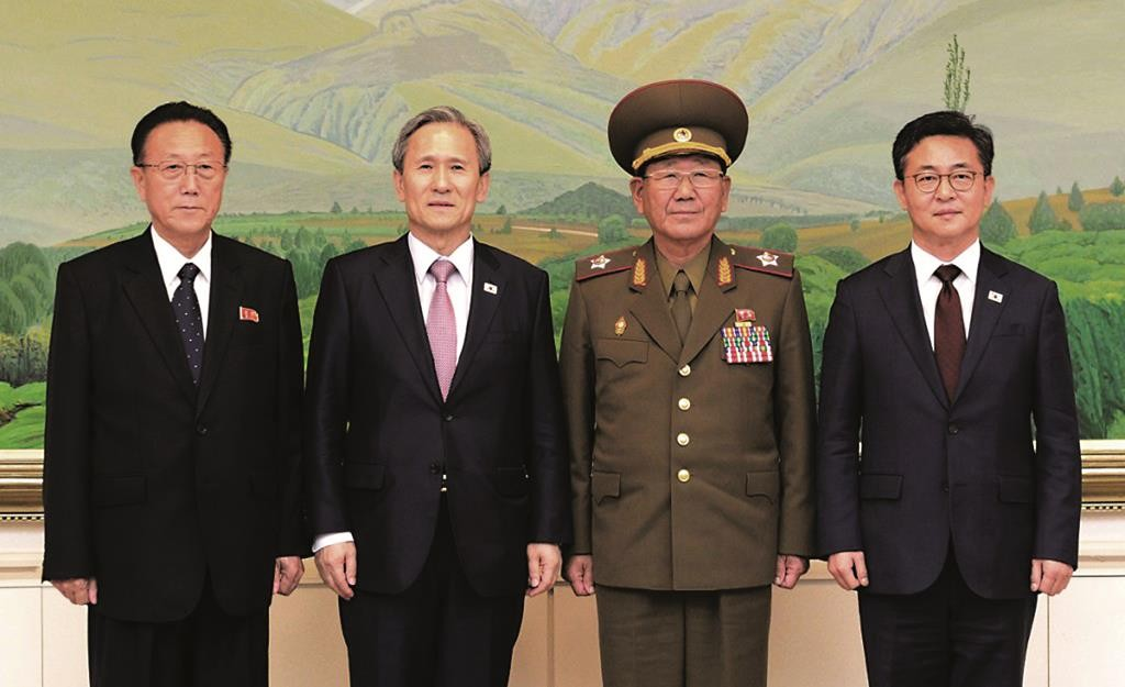 North and South Korean officials pose after their meeting at the border village of Panmunjom in Paju, South Korea, on Tuesday.  (The South Korean Unification Ministry via AP)