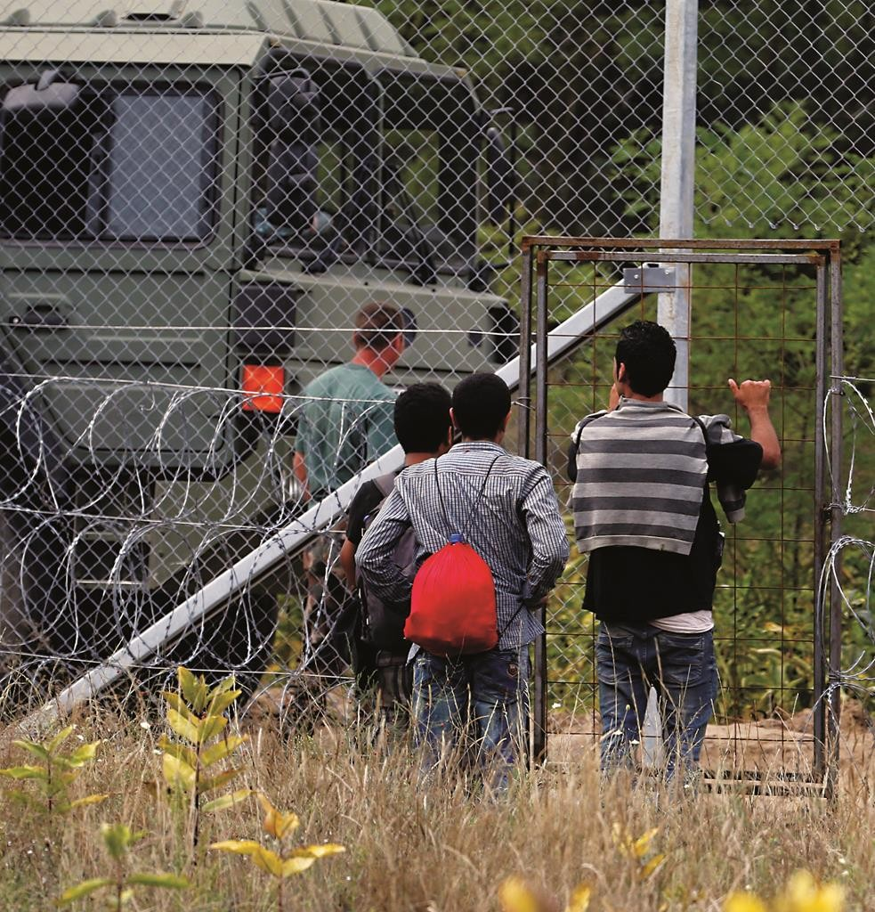 Migrants from Syria waiting at the gate in a wire fence on the Serbian border with Hungary, near Hajdukovo, Serbia, Tuesday. (AP Photo/Darko Vojinovic)
