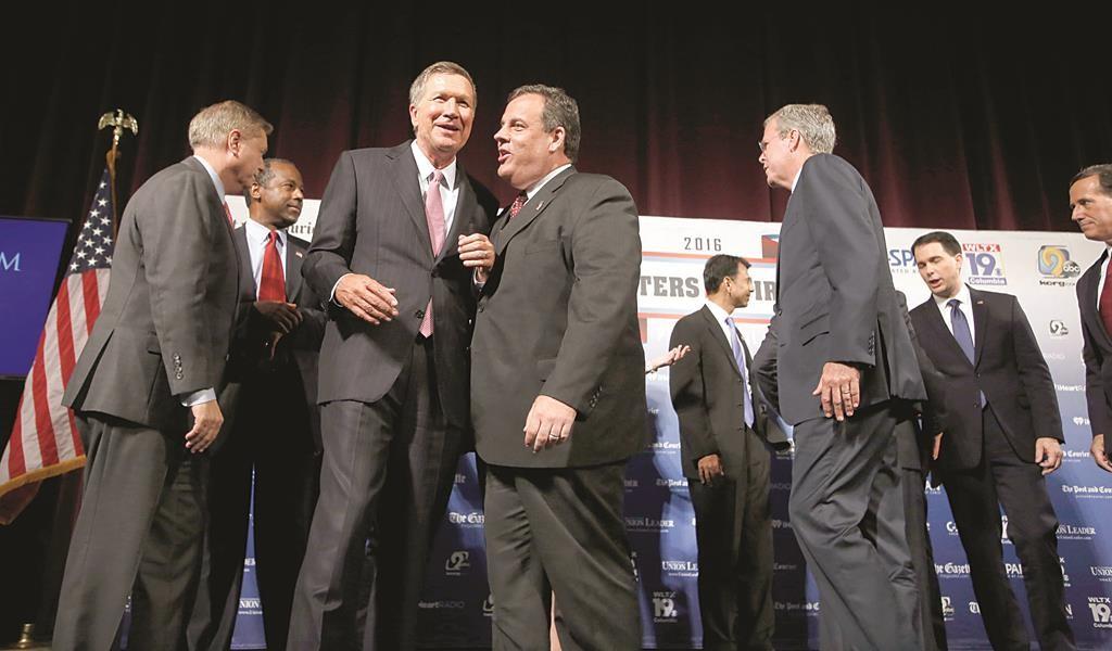 Republican presidential candidates, from left, Lindsey Graham, Ben Carson, John Kasich, Chris Christie, Bobby Jindal, Jeb Bush, Scott Walker and Rick Santorum speak among themselves after a forum Monday, in Manchester, N.H.  (AP Photo/Jim Cole)