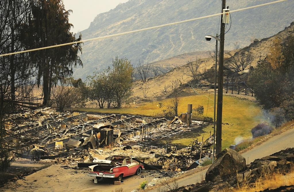 A burned structure along State Route Alt. 97 Monday, just outside of Chelan, Wash. Several large fires burning near the town destroyed dozens of homes and businesses.  (AP Photo/Ted S. Warren)