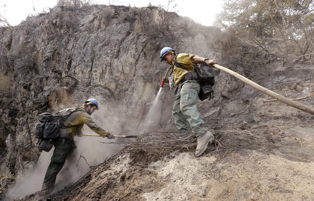 University of Alaska, Fairbanks, firefighting students Casey Lasota, left, and Harold Stein work to cool hotspots left from a wildfire Sunday, in Chelan, Wash.   (AP Photo/Elaine Thompson)