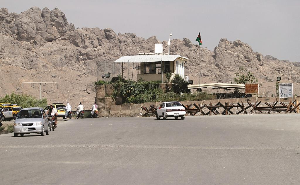 Afghans travel by motorbike and car in front of Mullah Mohammad Omar's house, in Kandahar province, south of Kabul, Afghanistan, Friday, July 31.  (AP Photo/Allauddin Khan)