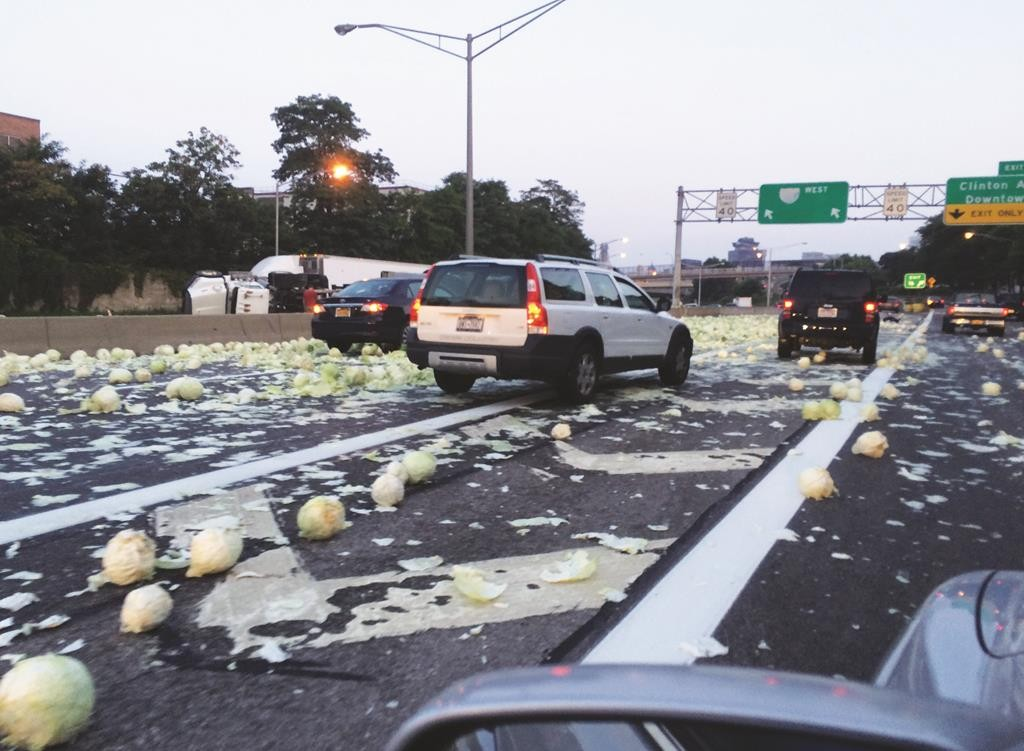 A truck carrying cabbage rolled over on Monday, dumping its load across a downtown Rochester road. (Tina Macintyre-Yee/Democrat & Chronicle via AP)
