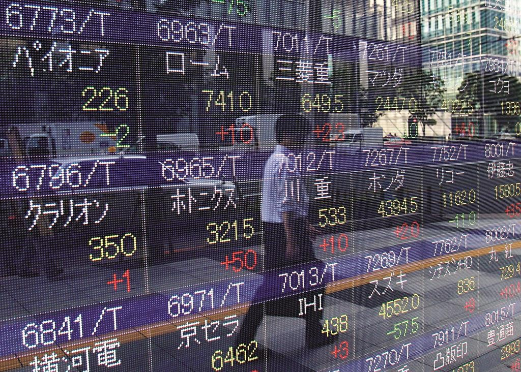 A man is reflected on an electronic stock indicator of a securities firm in Tokyo, Tuesday. (AP Photo/Ken Aragaki)