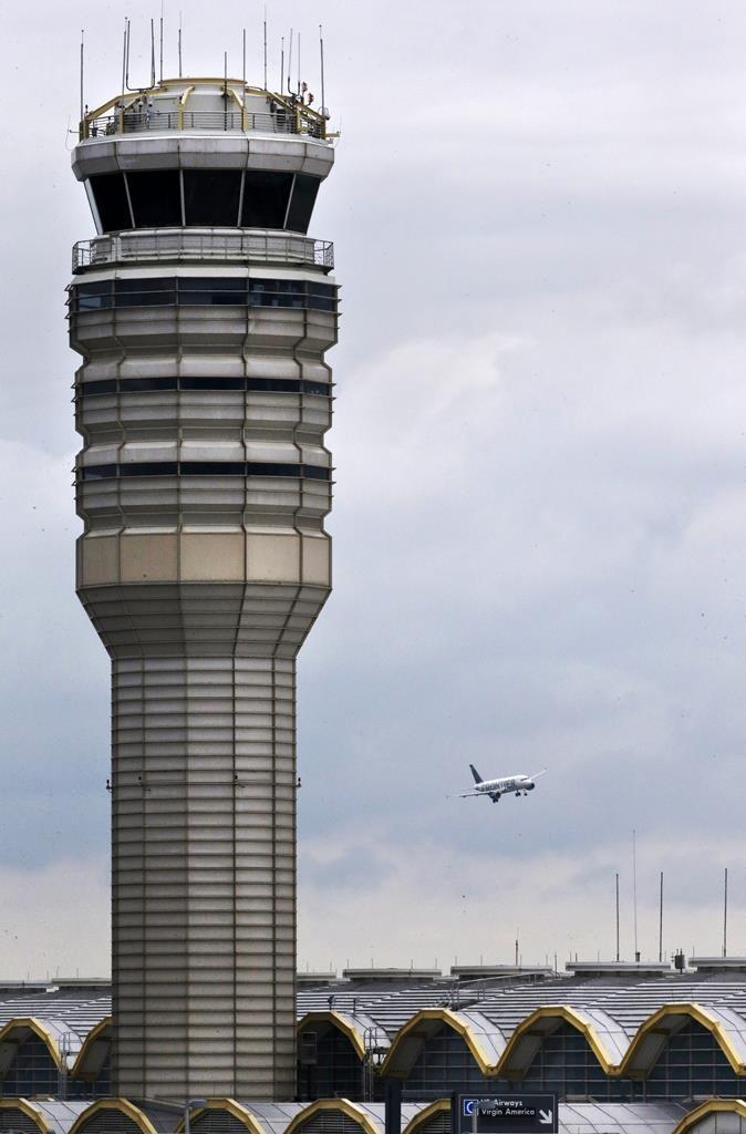 An airplane flies past the air traffic control tower at Washington's Ronald Reagan National Airport on Monday. (AP Photo/Jacquelyn Martin)