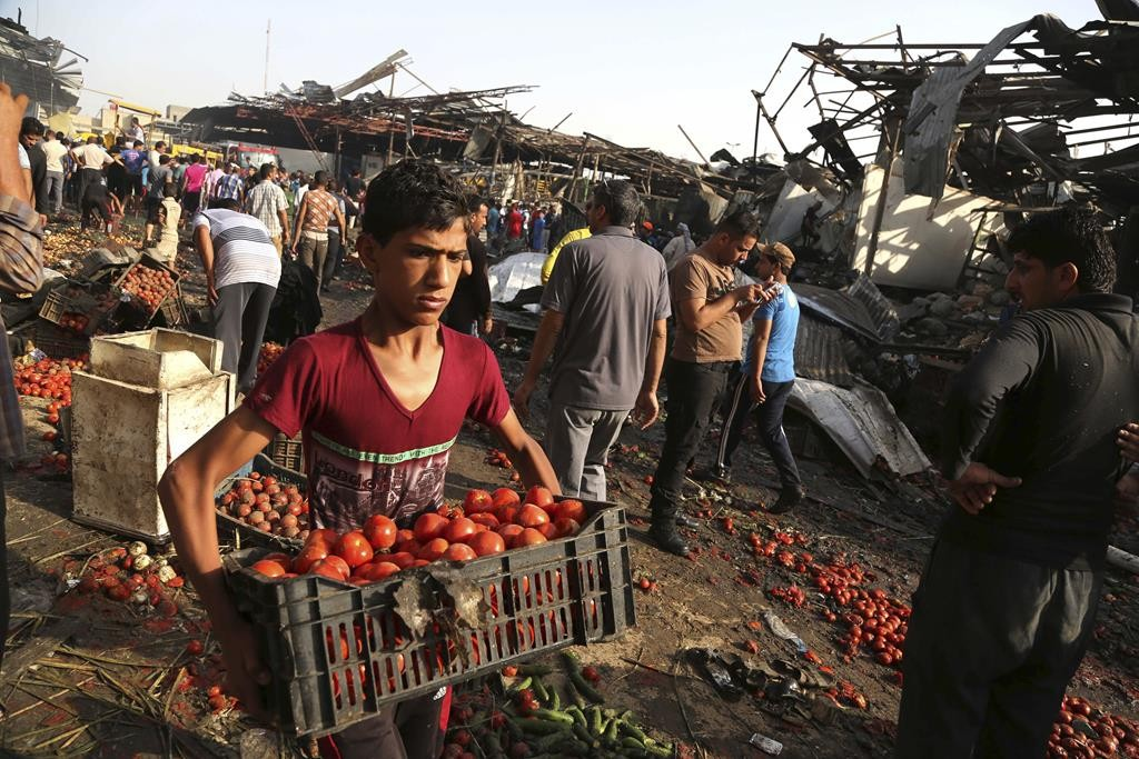 An Iraqi boy working for a grocery store collects his vegetables after a truck bomb attack in Jameela market in the predominantly Shiite neighborhood of Sadr City, Baghdad, Iraq, Thursday. (AP Photo/Karim Kadim)