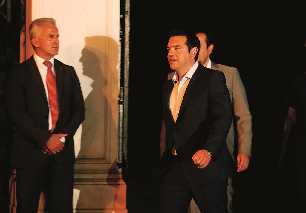 Greek Prime Minister Alexis Tsipras, center, leaves the presidential palace after a meeting with Greece's President, Prokopis Pavlopoulos, in Athens, Thursday.  (AP Photo/Petros Giannakouris)