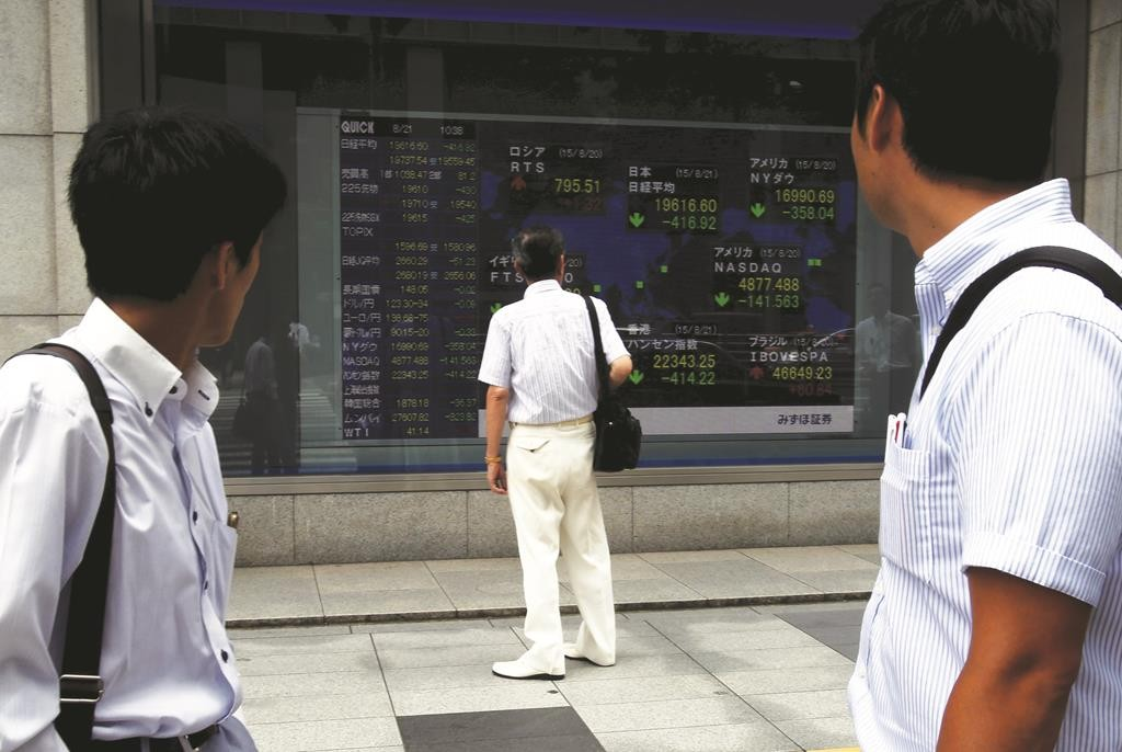 A man standing in front of an electronic board showing the stock market indices of various countries is seen between pedestrians outside a brokerage in Tokyo, Japan. (REUTERS/Yuya Shino)