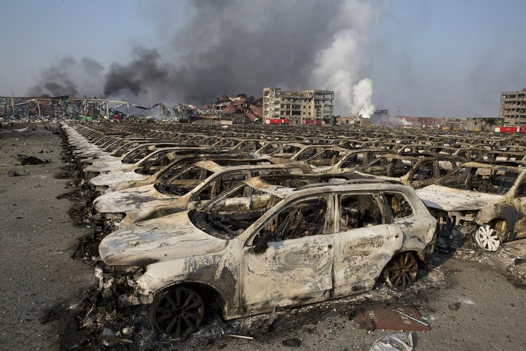Smoke billows from the site of an explosion that reduced a parking lot filled with new cars to charred remains at a warehouse in northeastern China's Tianjin municipality, Thursday. (AP Photo/Ng Han Guan)