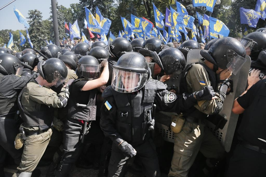 Police and protesters of the nationalist Svoboda (Freedom) party clash near the Parliament, in Kiev, Ukraine, after a vote to give greater powers to separatists in the east, Monday. (AP Photo/Efrem Lukatsky)