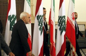 Iranian Foreign Minister Javad Sarif (L) walks near Lebanese and Iranian flags upon his arrival at the Government Palace in Beirut, Lebanon Tuesday. Zarid visited Lebanon for the first time since Iran reached an agreement with world powers on the country's nuclear agreement. (Reuters/Aziz Taher)