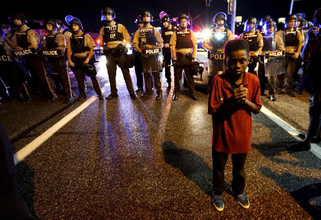 Amarion Allen, 11 years old, stands in front of a police line shortly before shots were fired during a protest in Ferguson, Missouri. (REUTERS/Rick Wilking)
