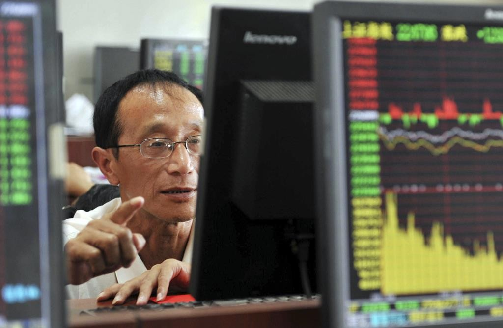 A Chinese stock investor monitors stock prices at a brokerage house in Hangzhou in eastern China's Zhejiang province on Tuesday. (Chinatopix via AP)