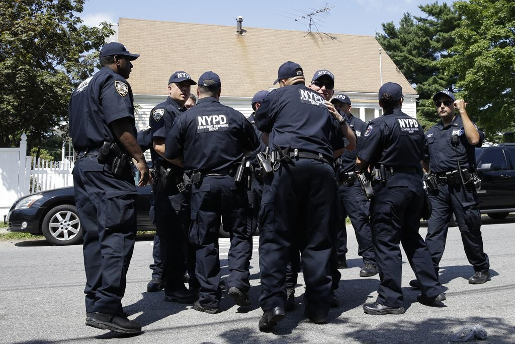 Police officers with the strategic response unit embrace Friday as they leave the scene of a standoff in Staten Island with Garland Tyree, who shot FDNY Lt. James S. Hayes. (AP Photo/Mary Altaffer)